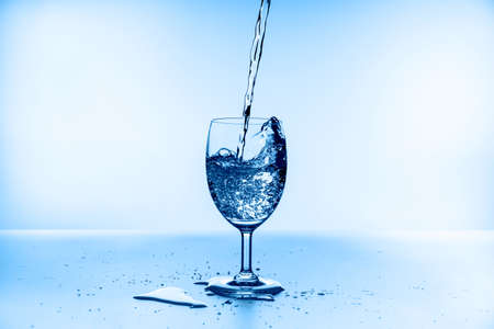 water splashing from glass isolated on blue background Standard-Bild - 155035644