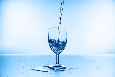 water splashing from glass isolated on blue background Standard-Bild - 155035645