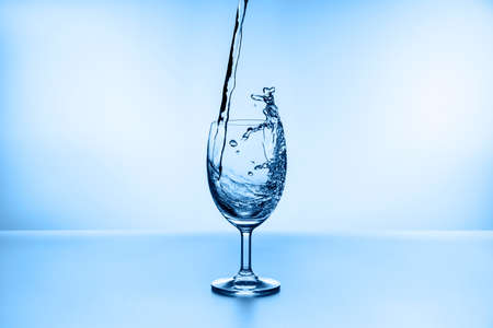 water splashing from glass isolated on blue background