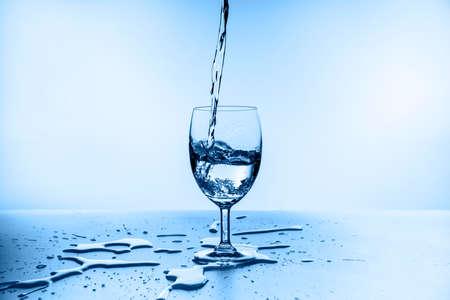 water splashing from glass isolated on blue background Standard-Bild - 155035693