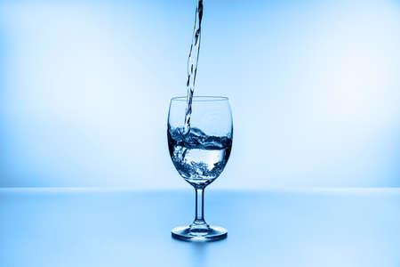 water splashing from glass isolated on blue background Standard-Bild - 155035700