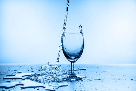 water splash collection in wine glass isolated on blue background Reklamní fotografie