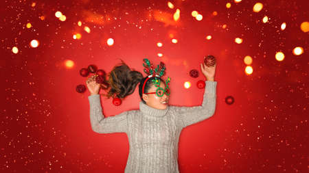 The girl is using the hand to hold the ball red decorations On a red background with christmas ornaments with led light. Top view. Christmas family traditions. Concept christmas.