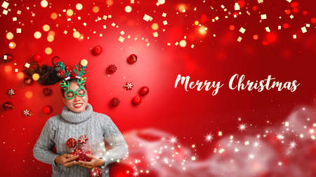 Christmas New Year. Young Woman dressed in warm sweater with  Props ball red with christmas ornaments in Holiday on shine red background. Concept merry christmas. Stock fotó