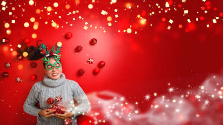 Christmas New Year. Young Woman dressed in warm sweater with  Props ball red with christmas ornaments in Holiday on shine red background. Concept merry christmas. Reklamní fotografie