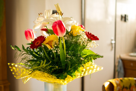 unfold: Flower bouquet with vase against blurry background. Stock Photo
