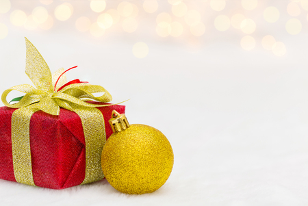 golden ball: Red Christmas gift box with shiny golden ball. Bokeh with glow effect on white background. Copyspace for your greeting or wishes Stock Photo