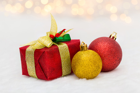 golden ball: Red Christmas gift box with shiny golden ball. Bokeh with glow effect on white background.