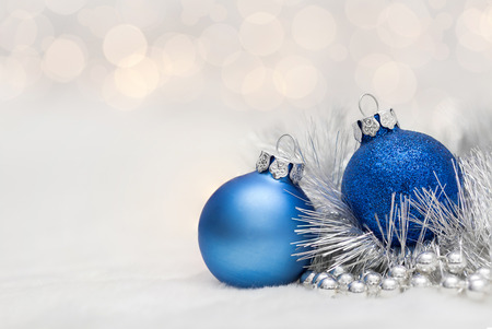 christmas fun: Blue Christmas balls with garland. Bokeh effect on white background. Copyspace for your greeting or wishes