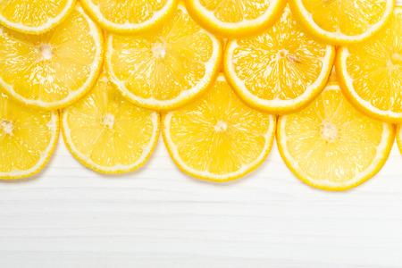lemon slices: Sliced lemons on white wooden surface, top view
