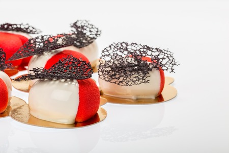 Group of french mousse cakes in form of heart, covered with red and white glaze Stock Photo