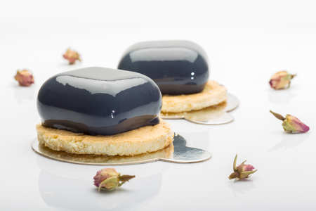 French mousse cakes on cookies covered with dark glaze on white background