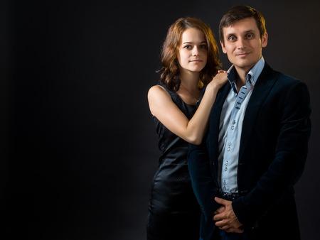 velvet dress: The Russian girl in black skin-tight dress hugging a guy in a velvet jacket Stock Photo