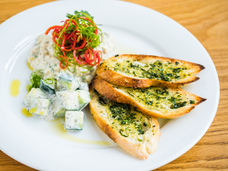 hummus with garlic bread and pepper on white plate and wooden table Stock Photo