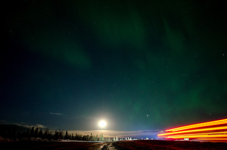 Light from the moon, headlights, taillights, and aurora light up the foresst north of Fairbanks as a truck heads up the Dalton Highway photo