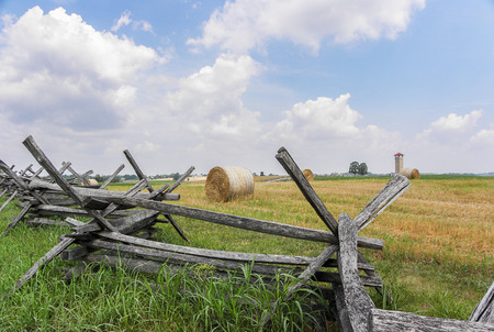split rail: Split rail fence in a lline to left offsets rolled hay bales  Stock Photo