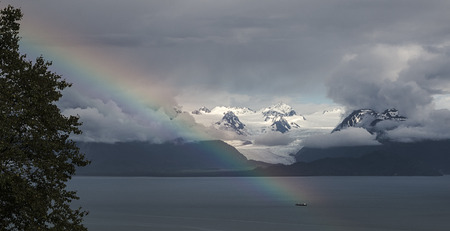 A rainbow shines in front of Grewingk Glacer in Homer Alaska Stock Photo