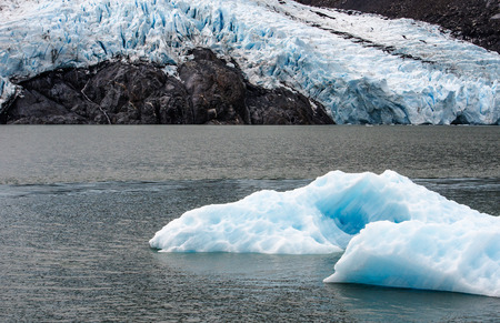 calved: A calved iceberg from Portage Glacier is seen against the glacier  Stock Photo