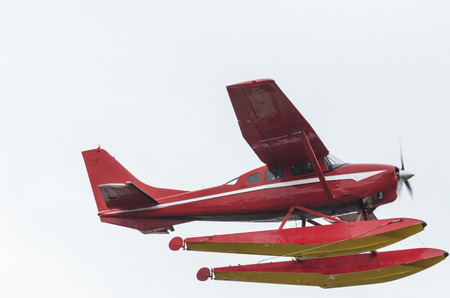 A red float plane flies over head against a washed out sky Stock fotó