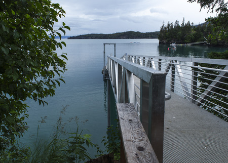 hand rails: A silver metal dock leads to the water of the Kachemak Bay   Maybe the kayaks in the distance will dock at it