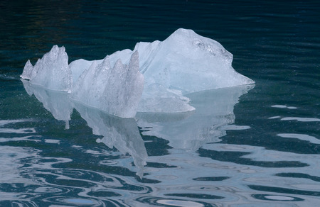 The many facets of a small chunck of reflects off the glacier blue water