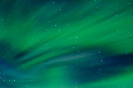 Auroras leave streaks of green across the sky. Stock Photo