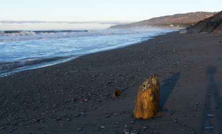stillness: Shadows throw a stillness to the crashing waves onto the beach Stock Photo
