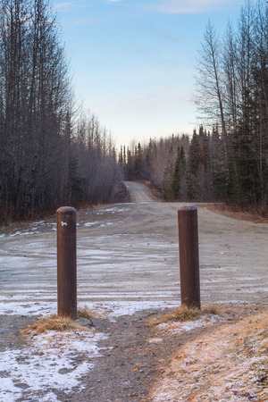 Two pipes mark the gateway to a rural gravel road.
