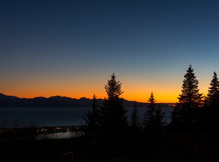 heralds: Bright orange heralds the last colors of sunset over Homer Alaska.