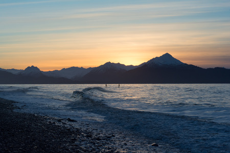 surfers: Two surfers paddle out in light waves on Kachemak Bay in southcentral Alaska. Stock Photo