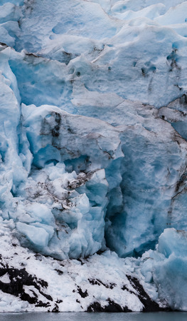 Large blocks of ice on a glacier face are posed to fall into the water.