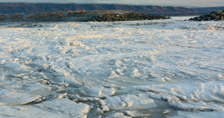 An ice floe is jammed up against a gravel bar on its way to the sea. Banco de Imagens - 37206117