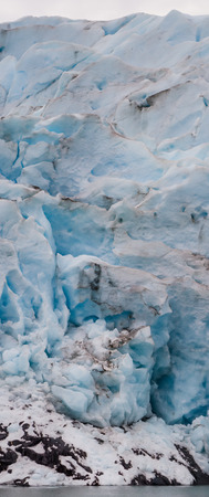 Blue blends with white across the face of glacier between water and sky.