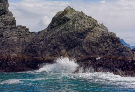 rocky point: The white spray of a crashing wave splashes up on a rocky point.