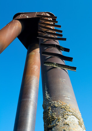 rungs: Bend metal rungs serve as a ladder up a ship sized piling. Stock Photo