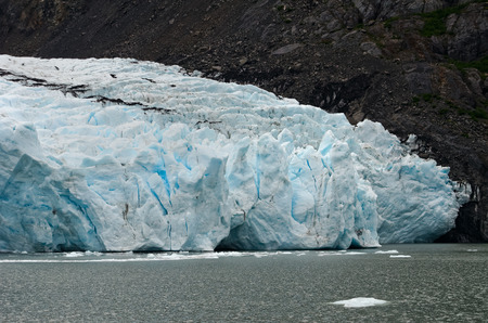 pushes: A blue white glacier pushes on a body of water. Stock Photo