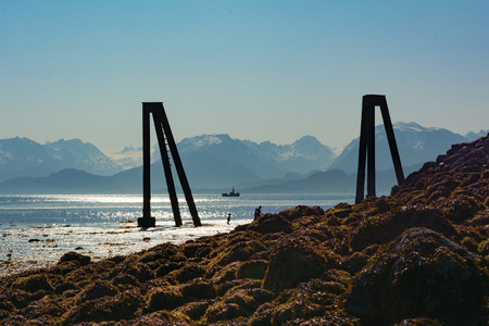 pilings: A mother and children explore a beach next to exposed ship pilings.
