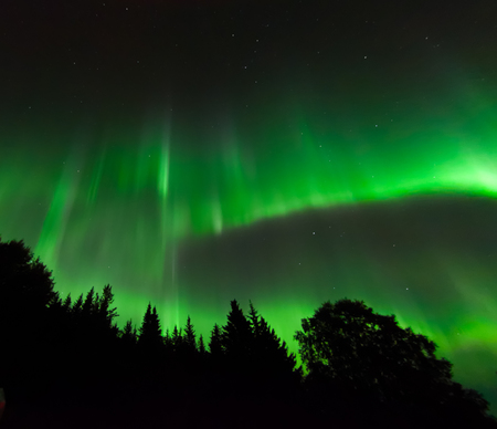 ionosphere: A green aurora draws a half circle across the northern sky