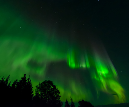 ionosphere: An aurora swirls into a pattern of a stream eddy but in patterns of green.
