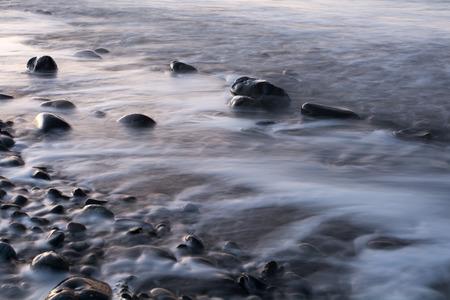 Long exposure has waves leaving white foamy streaks on a rocky beach.