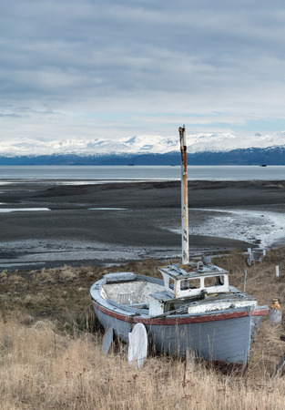beached: A weathered boat is beached forever amongst dry grasses with bay and mountainins in the background. Stock Photo