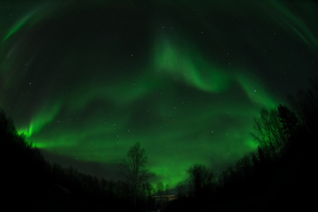 ionosphere: Waves of aurora build up in the Alaska night sky forming an outline of a mountain peak.