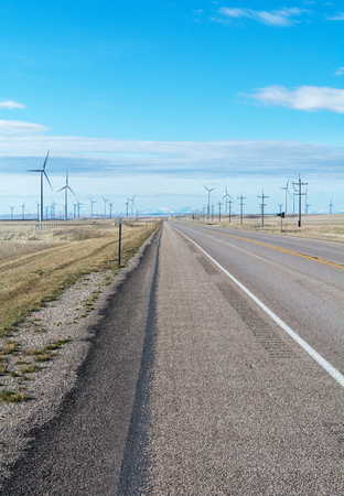 swept: A wind swept pairie cut by a orad and dotted with wind turbines