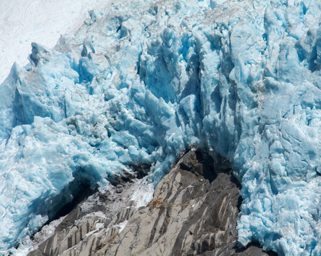clues: Dark streaks on the rock fall are clues to the rate of melting by the blue glacier ice.