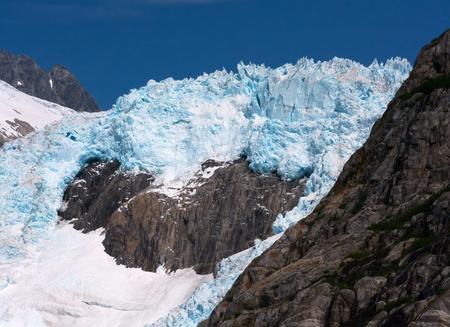 ridgeline: The white and blue of a glacier push around a stony ridge.