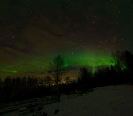 ionosphere: The glow of a city is caught by low clouds while a green aurora fills the sky above.