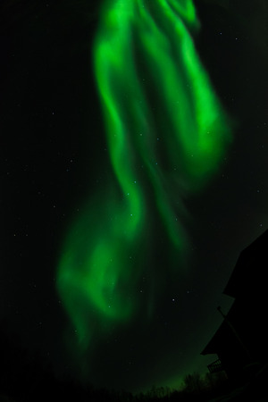 The swirls of an aurora have spread out dissolving into to mist over the house.