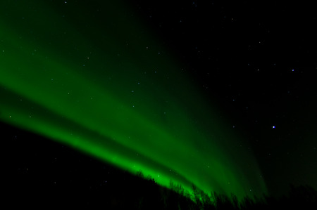 ionosphere: A wall of green light curves across the night sky.