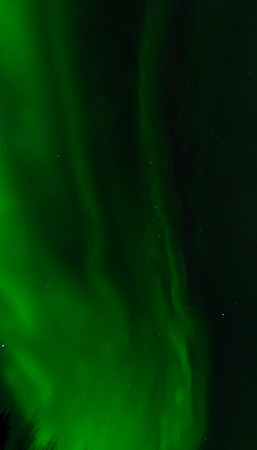 ionosphere: Swirling across the sky, a aurora leaves behind a green mist. Stock Photo