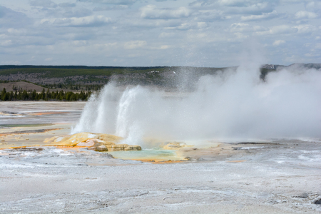 jets: Jets from an erupting geyser send water and mist across a white plain. Stock Photo